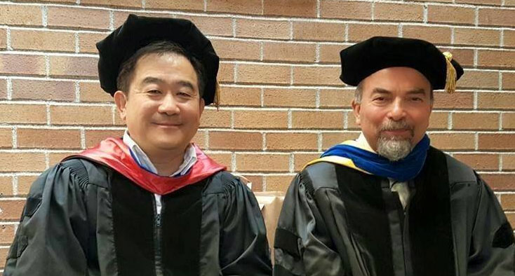 Professors Alex Jen and Mehmet Sarikaya in graduation gowns